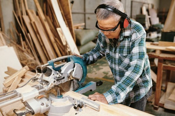 Experienced elderly carpenter in protective goggles and earmuffs cutting wooden planks with circular saw